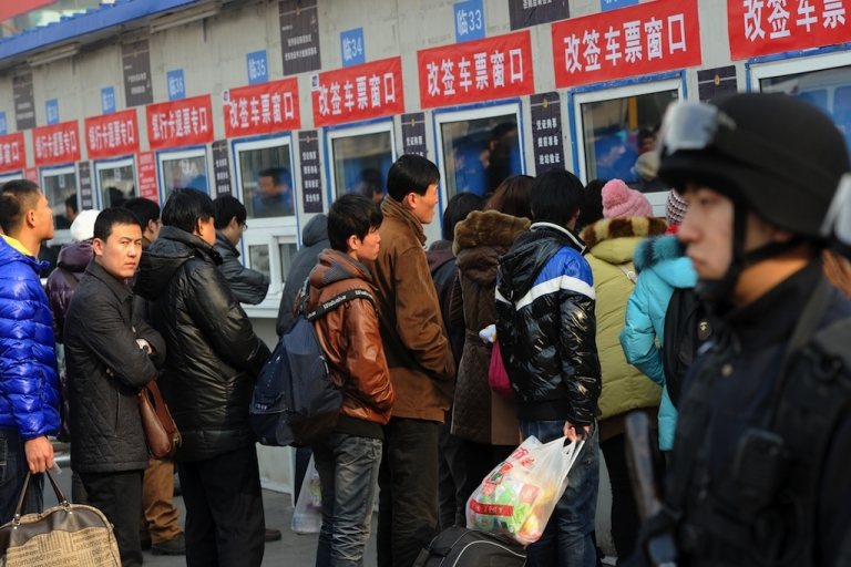 <p>Chinese police keep watch as migrant workers and students buy train tickets home for the annual Chinese New Year holidays, at the Beijing Train Station on Jan. 15, 2012. The world's largest annual migration of people begins in China on Jan. 15 with millions of travellers boarding public transport to journey across the vast country for the Lunar New Year celebrations.</p>