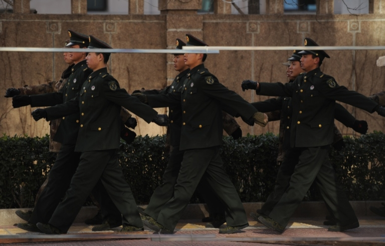 <p>PLA soldiers march in front of the apartment complex where jailed Nobel peace laureate Liu Xiaobo's wife lives in Beijing on December 10, 2010.</p>