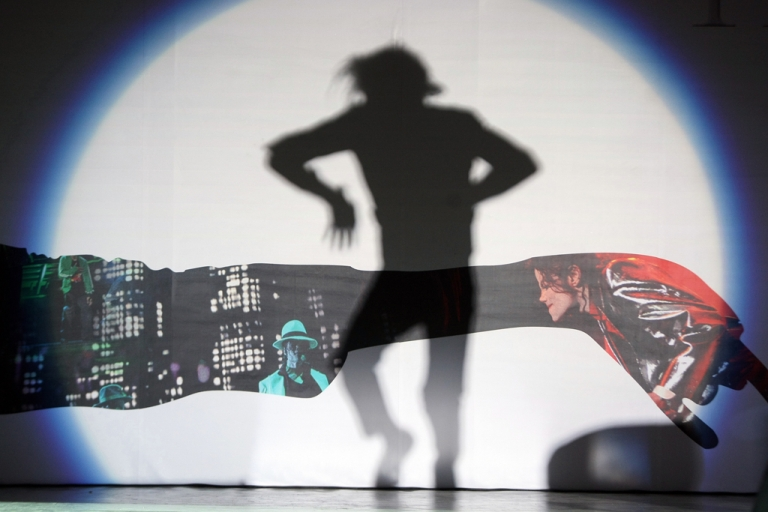<p>The shadow of a Michael Jackson impersonator from China is cast as he performs for thousands of fans gathered outside the Saga Cinema in Beijing on October 27, 2009.</p>