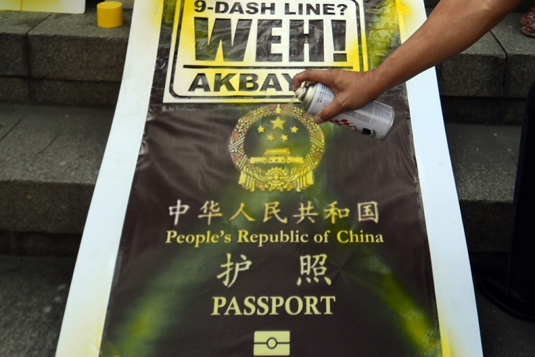 <p>Placard featuring a mock cover of a Chinese passport during a demonstration in Manila on Nov. 29, 2012, against reports that Chinese passports contain a map showing most of the South China Sea as belonging to China.</p>