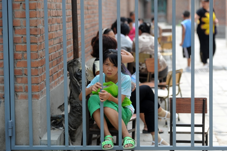 <p>A Chinese girl waits outside a school in the suburbs of Beijing on Aug. 10, 2010.</p>