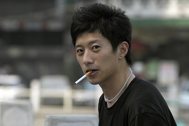<p>A young man smokes a cigarette in Beijing.</p>