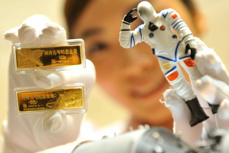 <p>A worker shows a pair of gold bars to mark the launching of China's Shenzhou-9 spacecraft in Beijing.</p>
