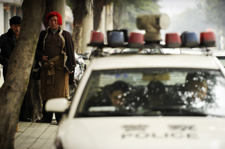 <p>Tibetans (L) walk next to a police car on a street in Chengdu in southwest China's Sichuan province on Jan. 27, 2012.</p>