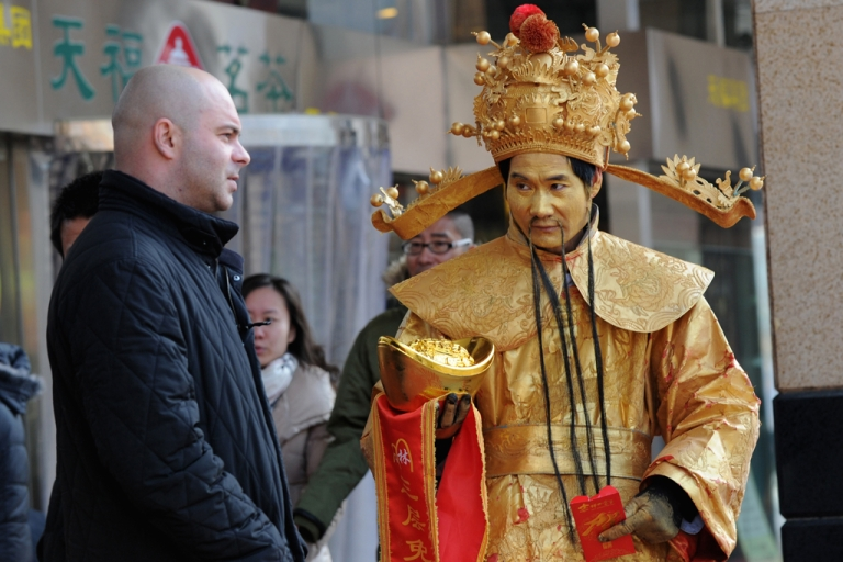 <p>China, which marks the 10th anniversary of its accession to the World Trade Organization on Dec. 11, has seen its GDP almost quadruple over the past decade, and exports and imports rise nearly fivefold. Here, a Chinese man dressed as a mythical figure hands out discount coupons to a tourist in Beijing.</p>