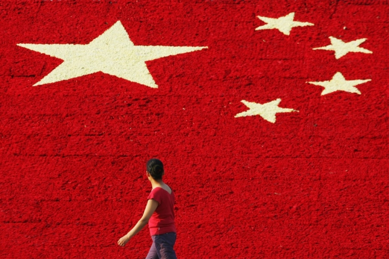 <p>A woman passes by the national flag made up of 100,000 carnations at Wuling Square September 25, 2007 in Hangzhou, China.</p>