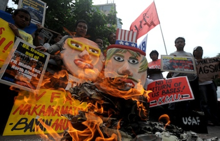 <p>Filipinos burn a US flag and a mock US stealth bomber while holding an effigy of Philippine President Benigno Aquino and Uncle Sam during a protest in front of the US embassy in Manila on January 28, 2012. The activists picketed the US embassy as they vowed to launch a campaign opposing the planned increased US military role in the Philippines.</p>