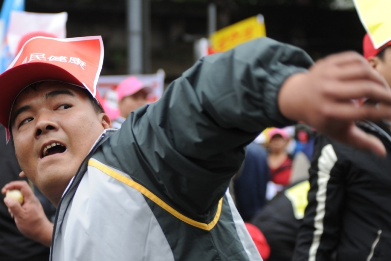 <p>A farmer throws eggs during an anti-US beef demonstration in front of Parliament in Taipei on March 8. Washington has recently urged Taipei to ease restrictions on US beef, while some local officials have said that stalled free-trade talks between the two sides hinge on the issue.</p>