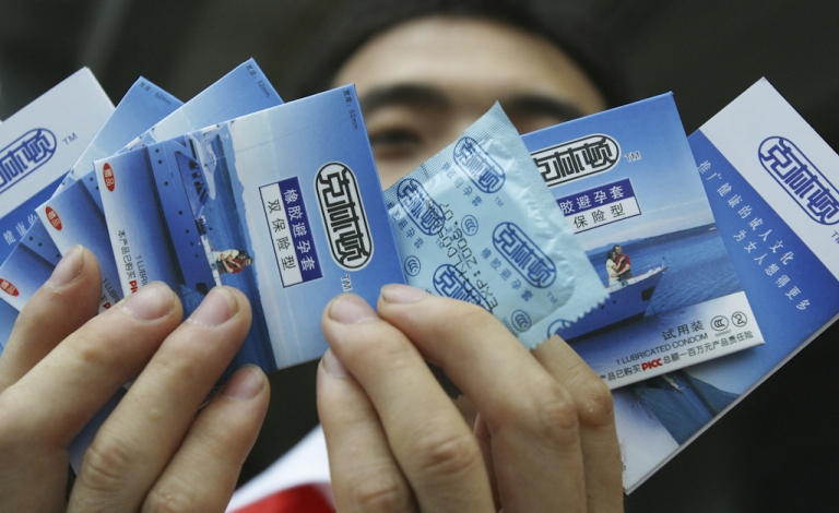 <p>A worker displays 'Clinton' brand condoms produced by the Guangzhou Haojian Bio-science Co during a promotion in Guangzhou, Guangdong province, China.</p>