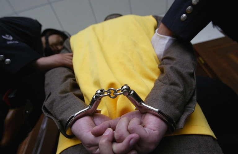 <p>Police escort a handcuffed suspect during a trial at the Meishan Intermediate People's Court on October 12, 2005 in the southwestern province of Sichuan.</p>