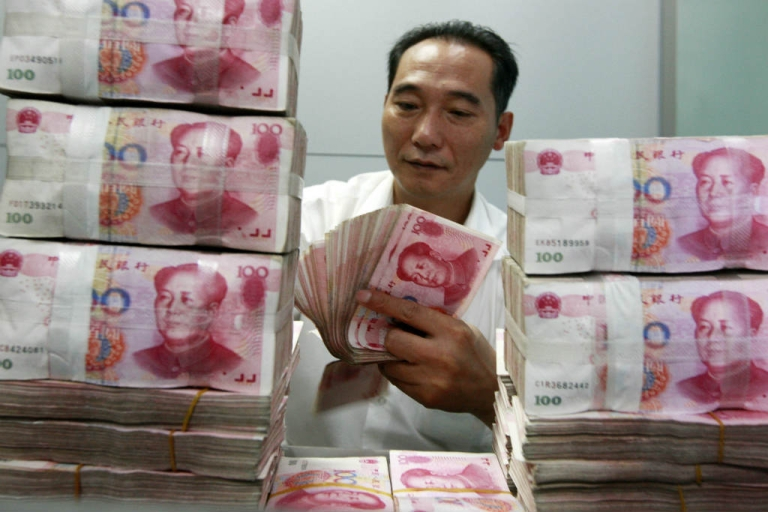 <p>A Chinese bank staff member counts stacks of 100-yuan notes. Many U.S. policymakers believe that China manipulates its currency.</p>