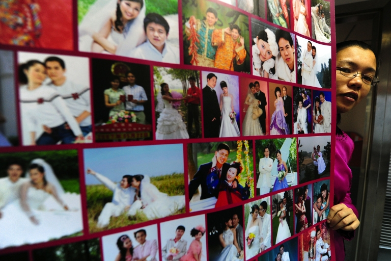 <p>The founder of a Chinese internet dating site poses in Beijing beside a poster of photographs of married couples who met on her website. A winning contestant on the TV dating show