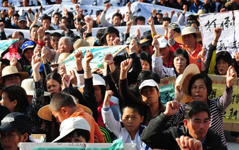 <p>Villagers hold banners and placards during a protest rally by residents of Wukan, a fishing village in the southern province of Guangdong, as they demand the government take action over illegal land grabs and the death in custody of a local leader on December 19, 2011.</p>