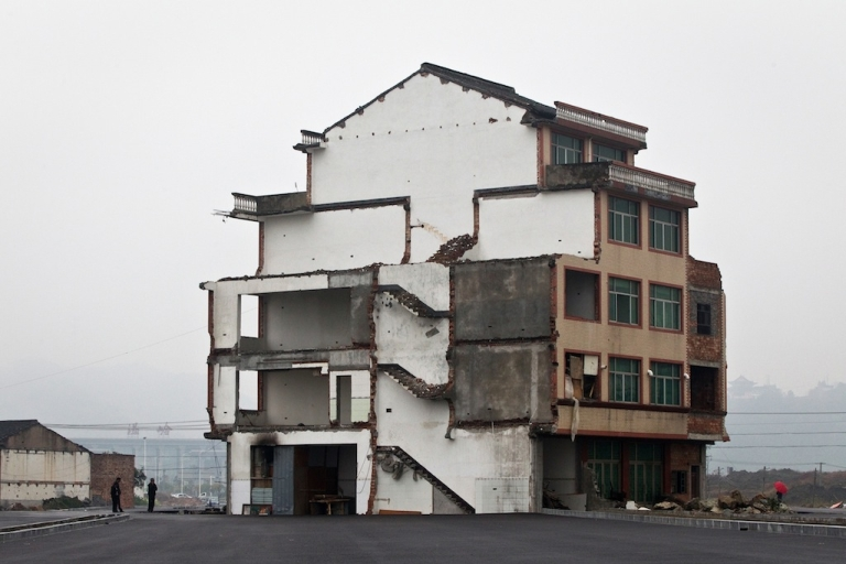 <p>A half-demolished apartment building standing in the middle of a newly-built road thanks to a Chinese couple that refused to move in Wenling, in eastern China's Zhejiang province, on Nov. 22, 2012.</p>