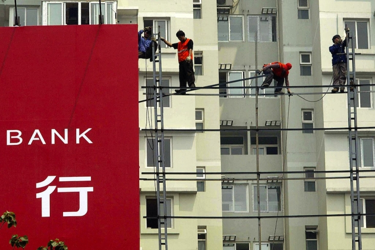 <p>Construction workers balance precariously in front of a nearly completed apartment building in Beijing. Housing sales are declining, but prices are still high.</p>