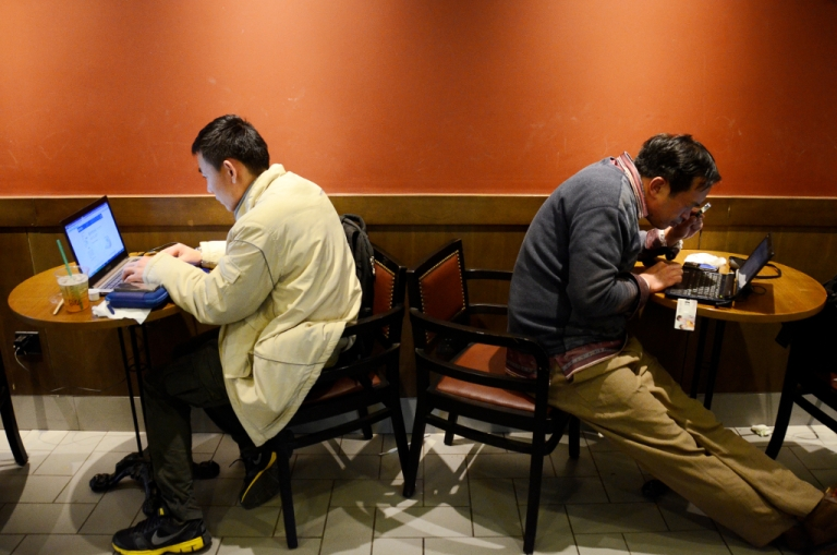 <p>Two Chinese men use their laptop computers at a cafe in Beijing on November 2, 2012. The Lei Zhengfu sex tape may implicate more officials on charges of bribery and corruption.</p>