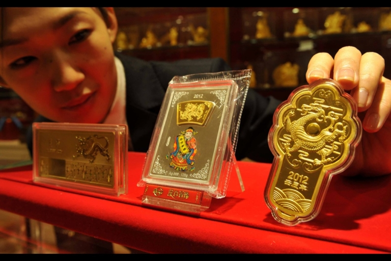 <p>A worker lays out a set of gold bars for at a gold shop in Beijing. Chinese consumer demand for gold increased dramatically in the last few years, according to the World Gold Council.</p>