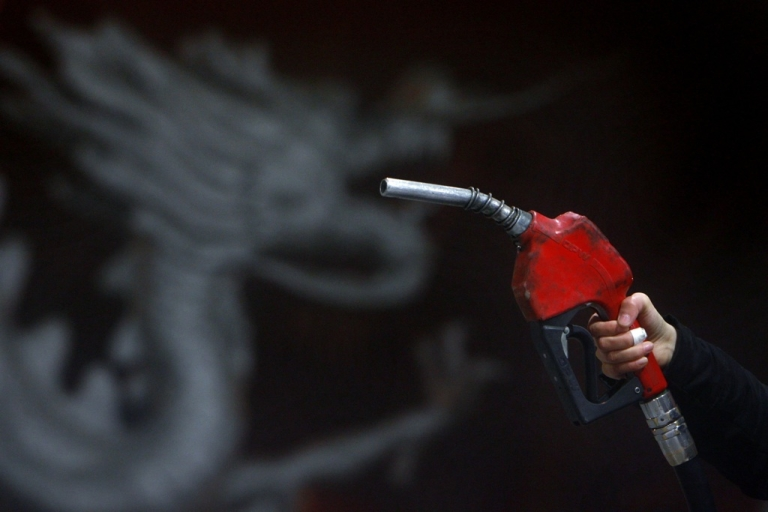<p>A worker fuels a car in front of a dragon decoration at a gas station January 14, 2007 in Beijing, China.</p>