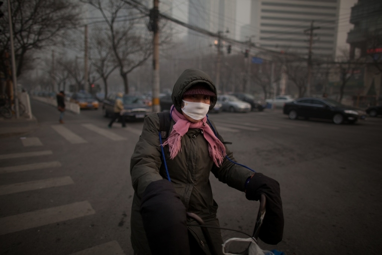 <p>A cyclist wearing a mask prepares to cross a street during heavy pollution in Beijing on January 12, 2013.</p>