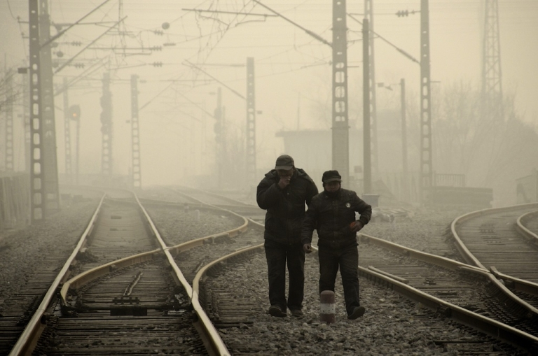 <p>This picture taken on Jan. 12, 2013, shows the dense smog in Beijing as two men walk along a railway line. The government is finally bowing to public outcry over the environmental situation in China.</p>