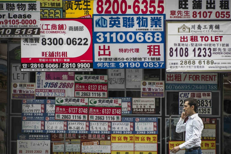<p>Billboards of real estate agents cover a wall in a street of Hong Kong..</p>