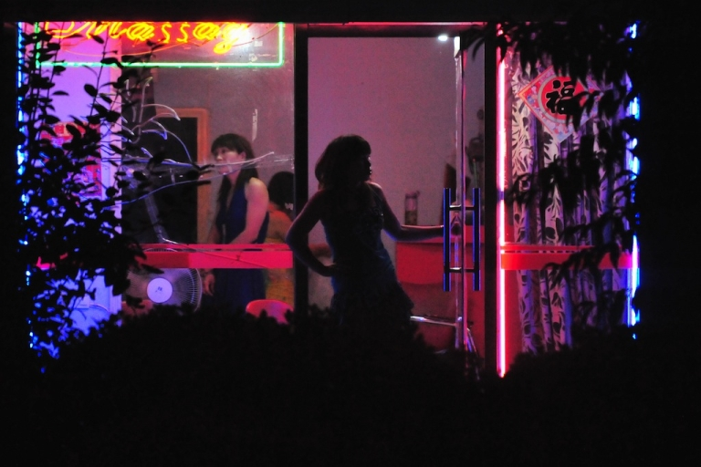 <p>A woman waits for customers in the doorway of a neon-lit barber shop in Beijing on July 9, 2008.</p>