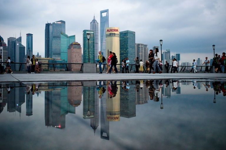 <p>Pedestrians walk past the skyline of the city's financial district in Shanghai in October 2010.</p>