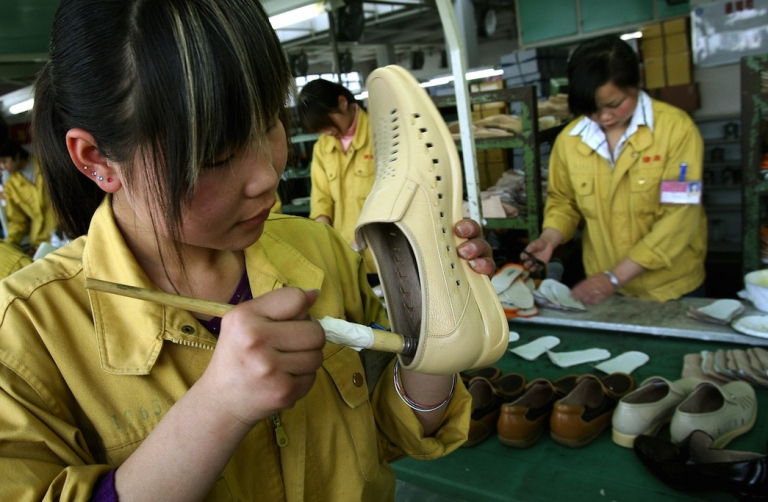 <p>A factory worker glues leather shoes on a production line at the Kangnai shoe factory in the Chinese city of Wenzhou. Small business and factories struggle to survive in current economic conditions.</p>