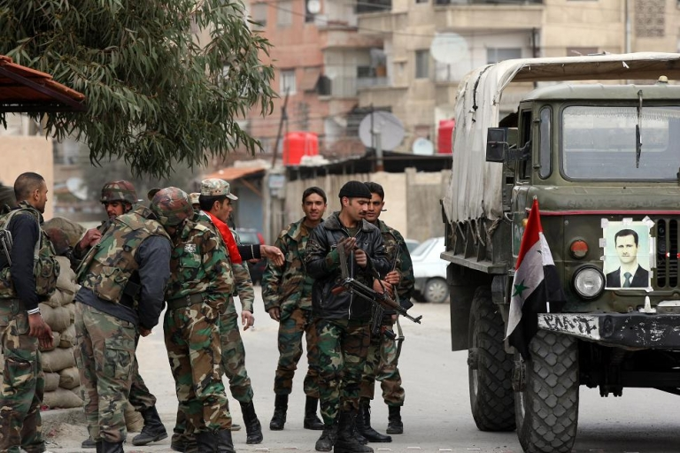 <p>Syrian army soldiers stand at a checkpoint in the city of Harasta, north of Damascus.  China has said it will send an envoy to Syria on Friday to assess the situation.</p>
