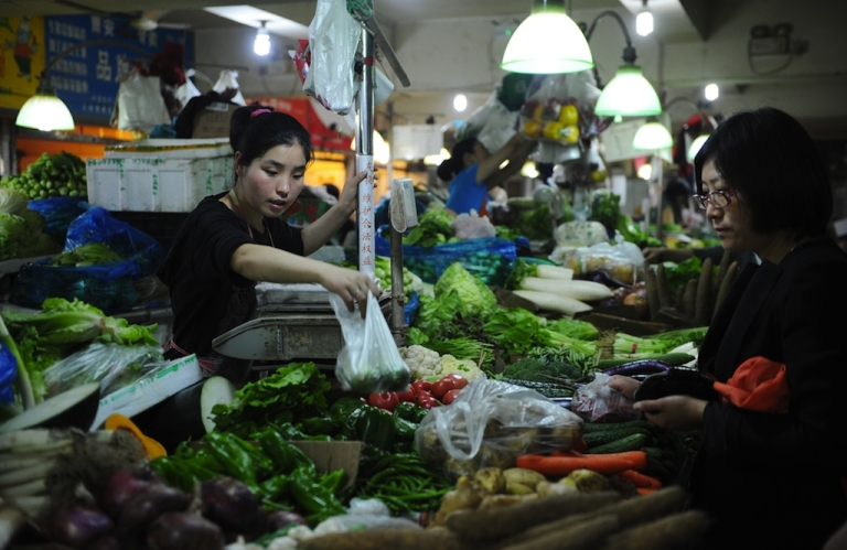 <p>Shoppers purchase vegetables at a market in Shanghai on May 23, 2012.</p>