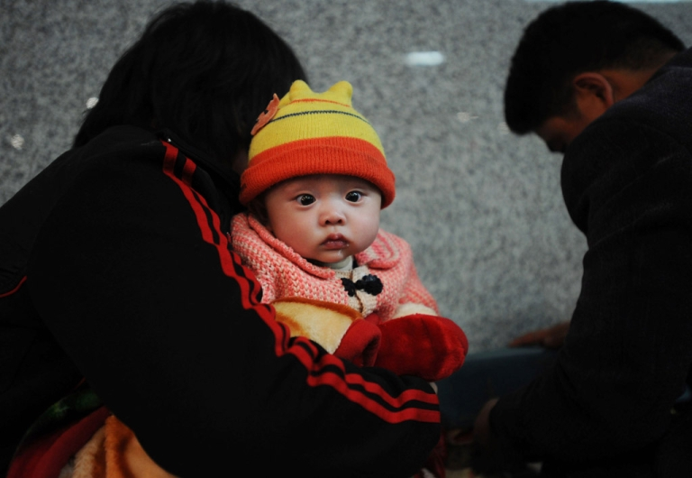 <p>A couple and their baby wait to board a train at the Wuchang Railway Station in Hubei Province, China.</p>