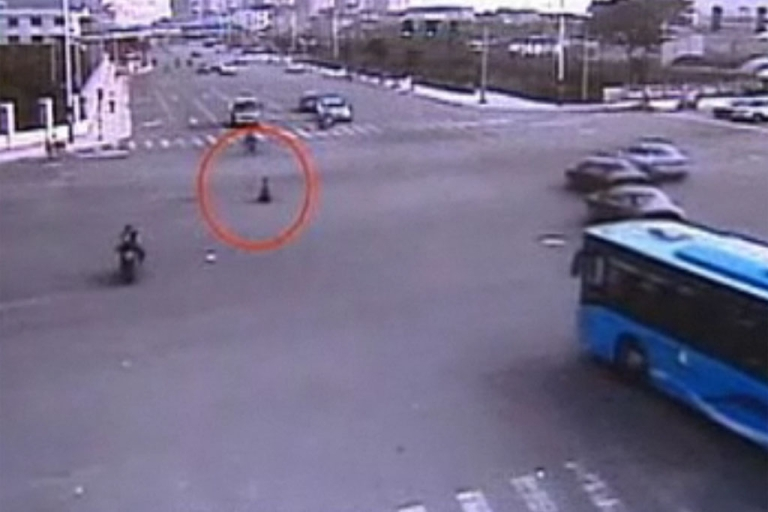 <p>A 3-year-old Chinese boy rides his toy motorcycle into traffic of a busy Wenzhou street.</p>