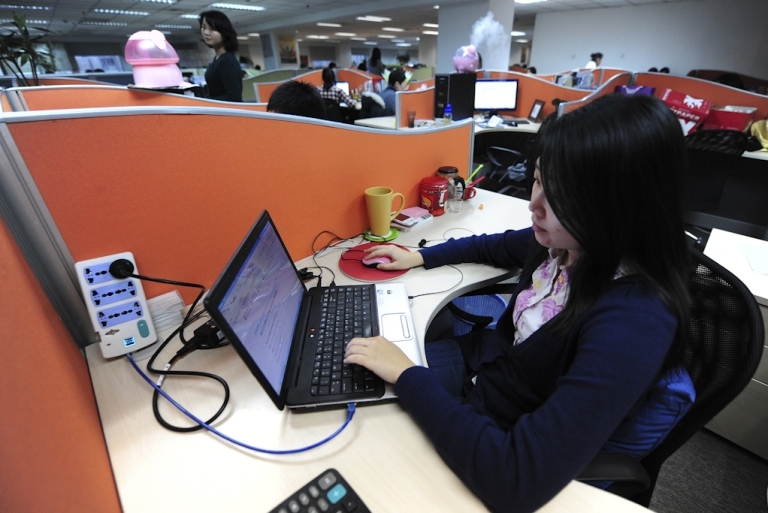 <p>A woman works online in her cubicle at an office in Beijing. China's homegrown social media sites like Sina Weibo are booming thanks to their better knowledge of the world's largest Internet market, and the censorship stifling foreign rivals like Facebook, Twitter, and Google-owned YouTube.</p>