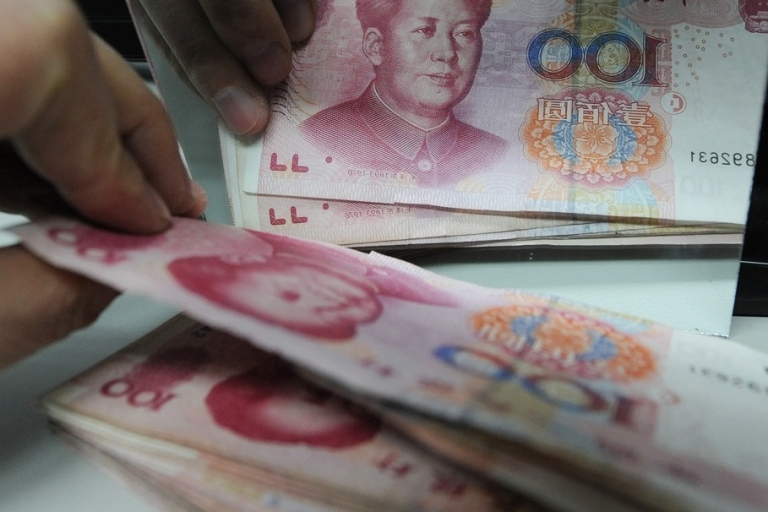 <p>A Chinese bank worker counts a stack of 100-yuan notes at a bank in Hefei, east China's Anhui province on February 27, 2011.</p>