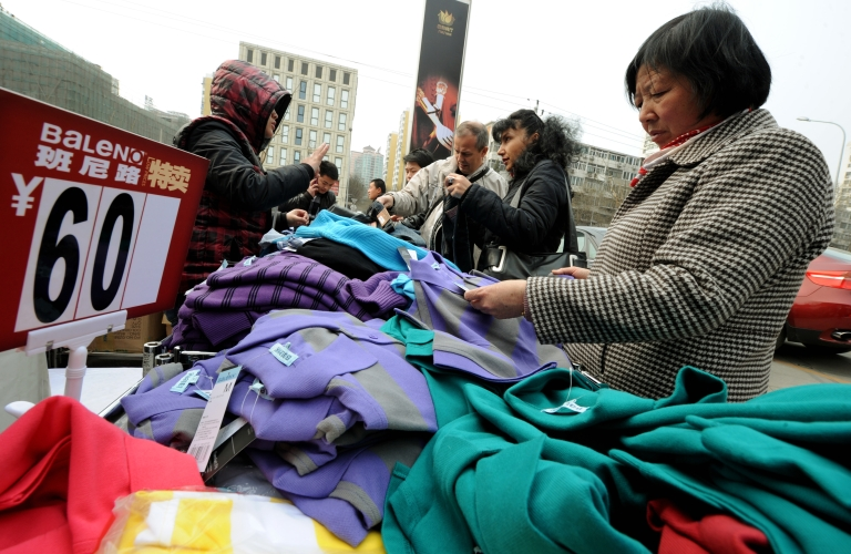 <p>Shoppers buy Chinese made clothing at a discount stall in Beijing on March 22, 2012.</p>