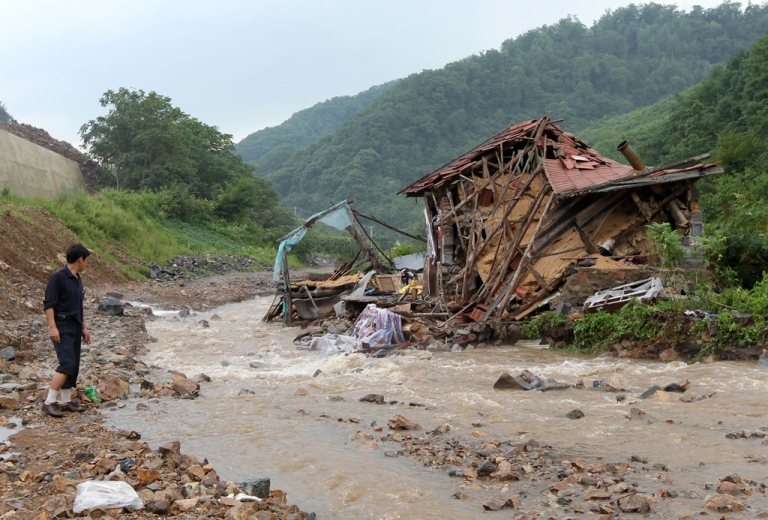 <p>A villager looks at a destroyed home after a flash flood swept through Kuandian, near the China-North Korea border in northeast China's Liaoning province on Aug. 21, 2010. Heavy rain sparked serious flooding along the border again this year.</p>