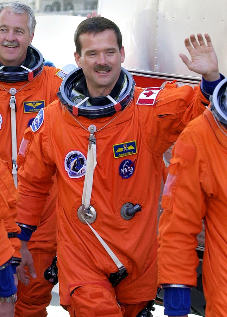 <p>Chris Hadfield of the Canadian Space Agency waves as he departs the Operations and Checkout building at the Kennedy Space Center in Florida. Hadfield is the first Canadian to ever be appointed commander of the International Space Stations.</p>