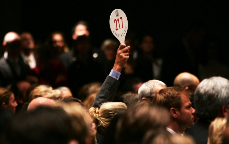 <p>A man holds his hand up while bidding on a work of art inside the Christie's auction house in New York City in 2006.</p>