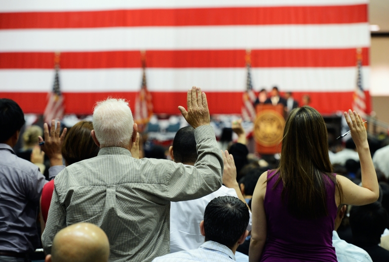<p>US citizenship candidates take the oath during a naturalization ceremony at the Los Angeles Convention Center on June 27, 2012.</p>