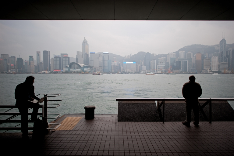 <p>People stand in the growing shadow of Hong Kong, where many rural residents are flocking to as their new home.</p>