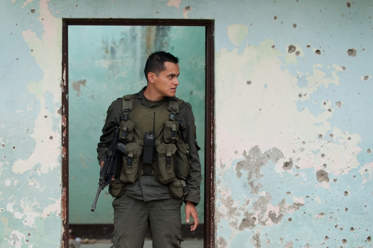 <p>A Colombian policeman guards a building full of bullet holes in the Colombian department of Cauca, where tensions have been mounting among Colombian security forces, the local indigenous population and the leftist guerrilla group the Revolutionary Armed Forces of Colombia, or FARC.</p>