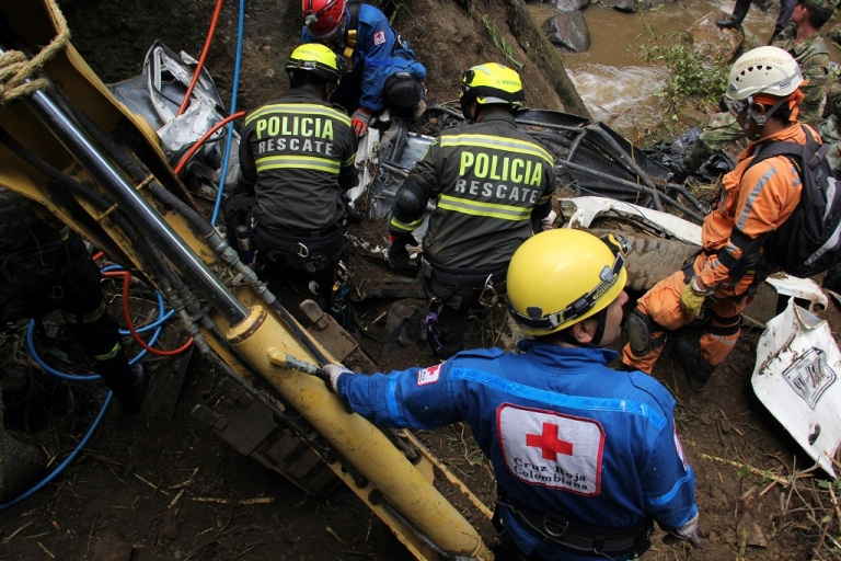 <p>Soldiers, policemen and Red Cross members search for victims on December 30, 2012, after a landslide along a road between the cities of Neiva and Florencia, in southwestern Colombia.</p>