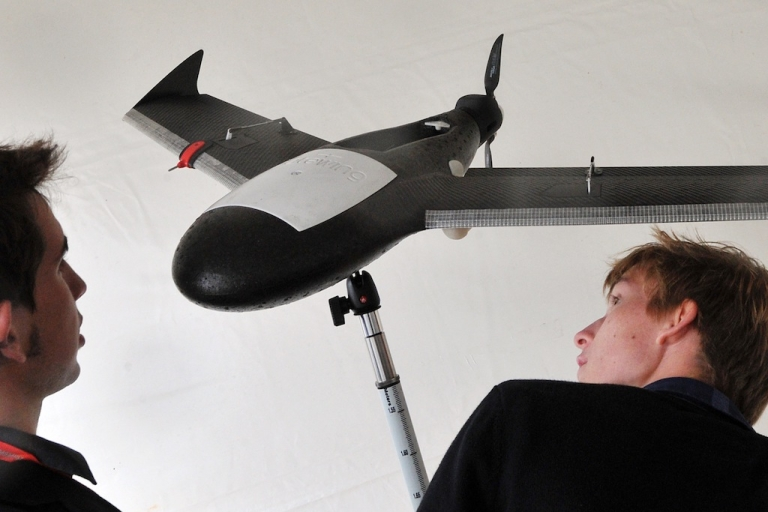 <p>People look at a Gatewing X100 drone, which could be used for commercial surveying purposes, on September 26 in Merignac near Bordeaux, during the UAV Show Europe, an International Drone fair.</p>