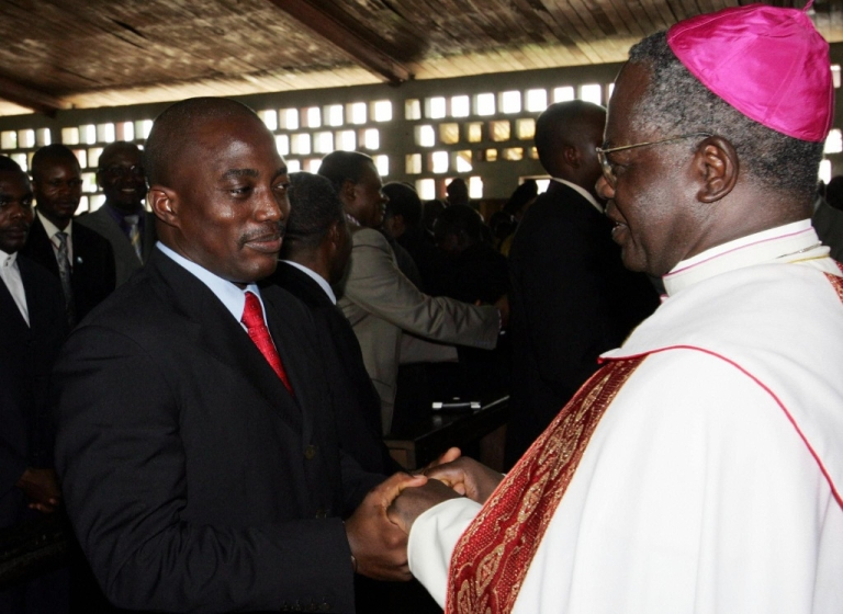 <p>Democratic Republic of Congo (DRC) President Joseph Kabila (L) shakes hands with Catholic Archbishop Laurent Monsengwo (R) at the end of an ecumenical ceremony, 17 October 2004 in KIsangani during his landmark visit to the troubled east of the vast central African country. The two-hour service was held at Saint Joseph's Church in Kisangani's Tchopo district, which was especially hard hit during the DRC's 1998-2003 war.</p>