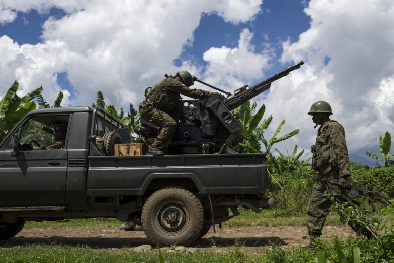 <p>A soldier of the Armed Forces of the Democratic Republic of the Congo (FARDC) walks past a truck-mounted machine gun in the bush of Jomba in restive North Kivu province on May 19, 2012. The Congolese army was engaged in an intense firefight with M23 rebels in the hills above the village of Kinyamahura, near  Bunagana, on the border with Uganda.</p>