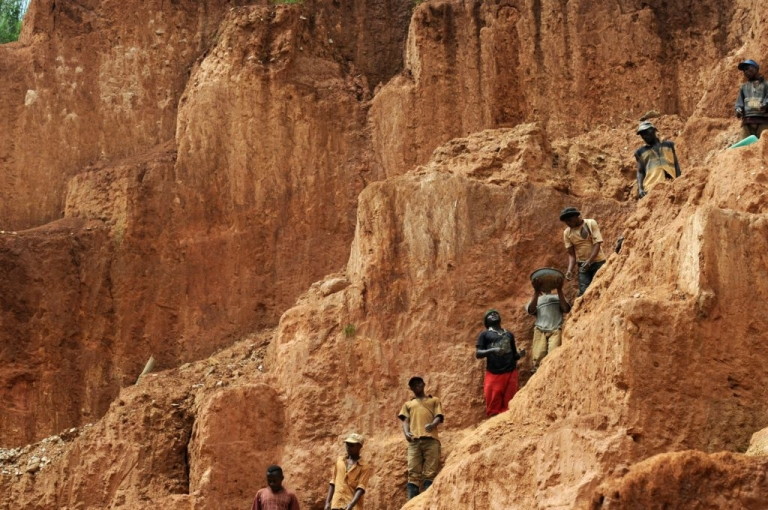<p>Workers stand on a muddy cliff as they work at a gold mine on Feb. 23, 2009 in northeastern Congo.</p>