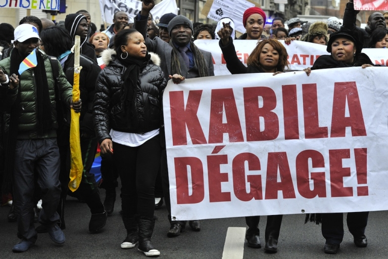 <p>Katumba's death places Congo at a more dangerous point even than last year's elections. Here, DR Congo demonstrators shout, holding a banner that reads,