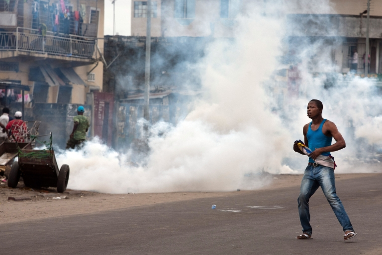 <p>A supporter of opposition leader Etienne Tshisekedi  stands next to tear gas fired by police to disperse demonstrators in Kinshasa on December 23, 2011. DR Congo police banned a swearing-in ceremony that day for opposition leader Etienne Tshisekedi, who held the event in his house after soldiers blocked the entrance to the stadium.</p>