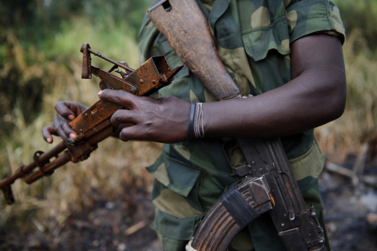 <p>An M23 rebel holds the burned remains of an AK-47 rifle near the village of Mabenga in the Democratic Republic of the Congo's restive North Kivu province on July 28, 2012.</p>