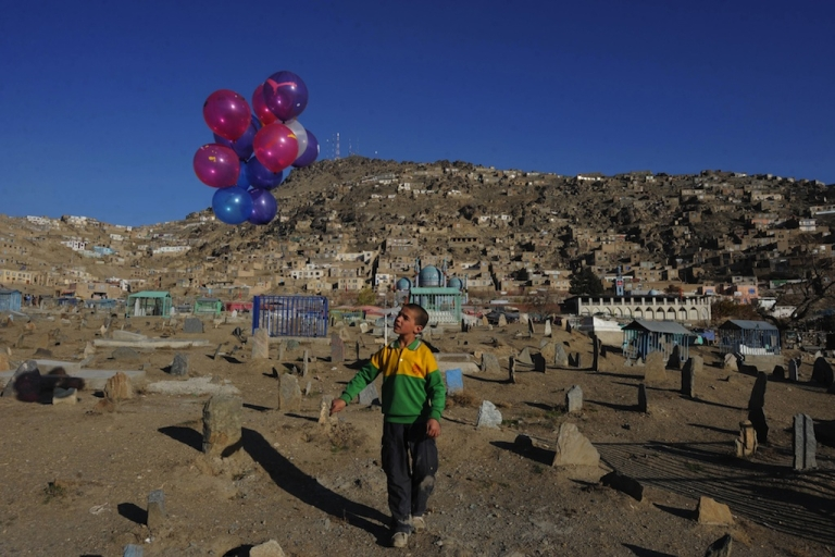 <p>Afghan child Abdul Wahid, 10, waits for customers as he sells balloons at a cemetery in Kabul on Nov. 30, 2011. A 13-year-old boy from Herat Province was recently sentenced to a year in prison for having sex with two adult men, in a case that's drawn the ire of human rights groups.</p>